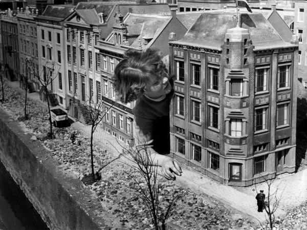 SFA001005090 Een meisje steekt haar hoofd door tussen enkele Amsterdamse miniatuurgrachtenpanden in Madurodam, Den Haag, Nederland, 1953.
