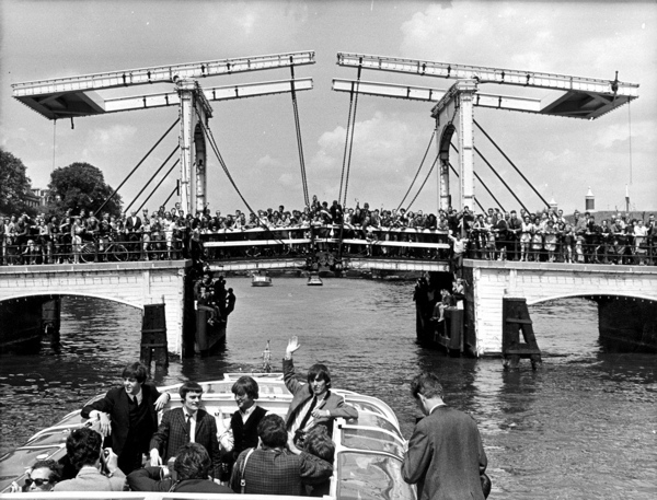 SFA001005312 Britse popgroep The Beatles in Nederland. Op een rondvaartboot varen ze door de Amsterdamse grachten, waar ze vanaf de Magere Brug door honderden fans worden toegejuicht. V.l.n.r. Paul McCartney, invallend drummer Jimmy Nichol, John Lennon en George Harrison die terugzwaait.  6 juni 1964.