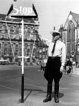 SFA001007573 Verkeersagent bij stopbord regelt het verkeer op de Dam in overhemd, vanwege de warmte, -Amsterdam, zomer 1953.