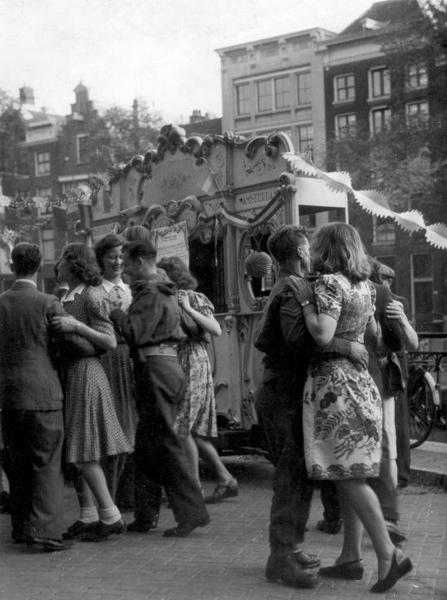 SFA001017150 Bevrijdingsfeesten in Amsterdam, 26 juni 1945. Dansen bij een draaiorgel aan een Amsterdamse gracht. Nederland.