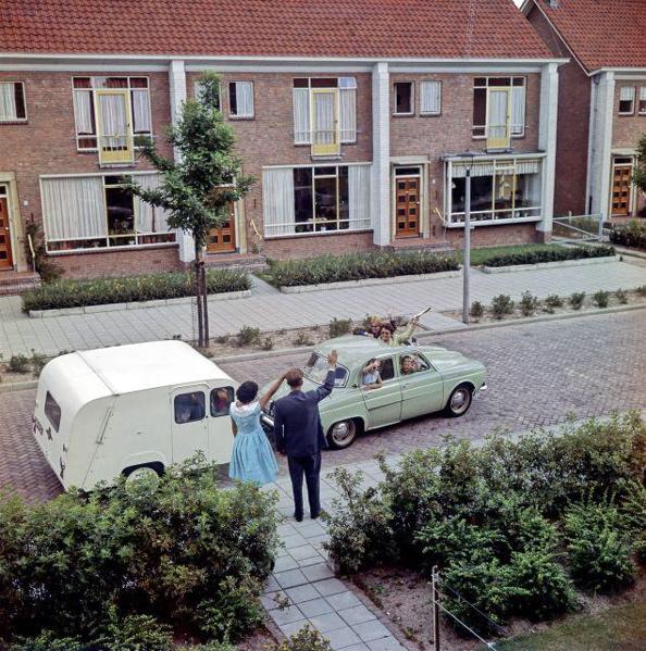 SFA001021162. Gezin uit jaren '50-nieuwbouwwijk gaat met auto ( Renault Dauphine ) en caravan ( Kip ) op vakantie, en wordt uitgezwaaid door mensen in de straat. [ buren of mensen die op het huis passen, o.i.d.]. Nederland [1964].
