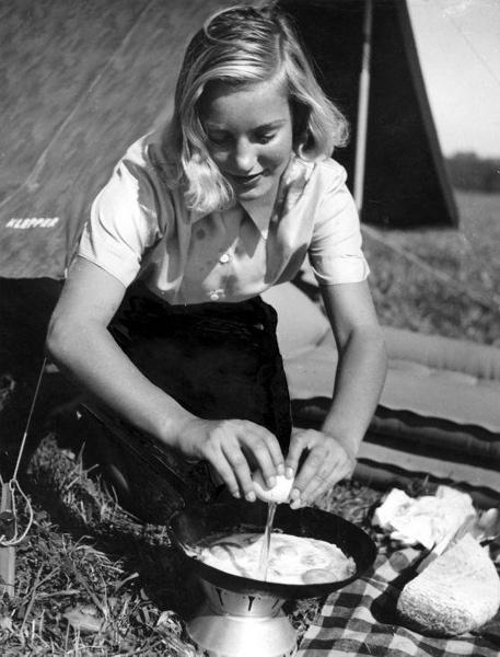 SFA001021189. Een meisje bakt tijdens het kamperen een heerlijk ei voor haar tent op een campingbrandertje. Plaats en datum onbekend.