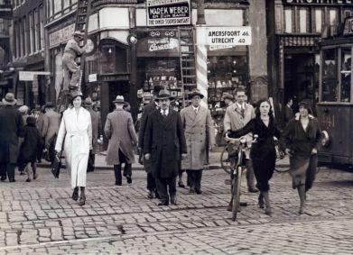 SFA002003212 Oversteken van voetgangers. Een tram is nog net zichtbaar rechts. Een ANWB-bord geeft de richting aan naar Amersfoort en Utrecht, Muntplein hoek Regulierbreestraat te Amsterdam, Nederland 1930-1934.