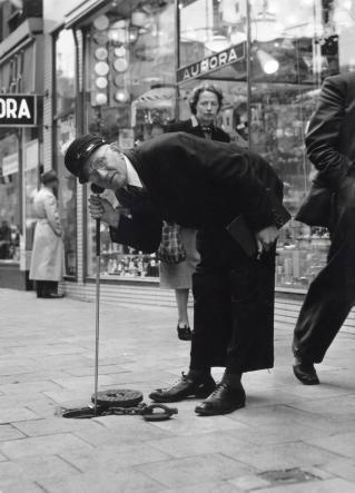 SFA002022612 Watervoorziening. Het zoeken naar lekken in de Amsterdamse waterleiding door een werknemer van het Gemeentelijke Waterbedrijf. Op de achtergrond de etalage van Aurora, een zaak in verlichtingsartikelen.12 juni 1953.
