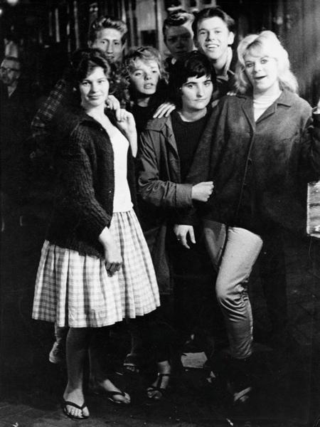 SFA004002137 Jongeren. Vier meisjes, van wie een met een rok met petticoat en drie jongens  staan in een groepje op straat in de Jordaan. Nederland. Datum onbekend.