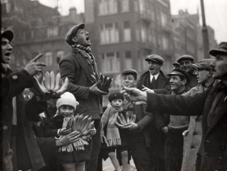 """SFA007003104 Straathandel. Handelaar in bananen prijst zijn fruit luidkeels aan, [Amsterdam] Nederland 1930-1940. Daaronder een paar kleine kinderen met een tros bananen. [Wellicht een sc讥 uit de Jordaan-klucht """"Waarom zijn de bananen krom"""", die werd opgevoerd door Willy en Karel Chanson; Willy Chanson eigen naam: Willem Munnik, (1884-1942), die samen met zijn broer optrad als het komisch duo Mie en Ko]."""