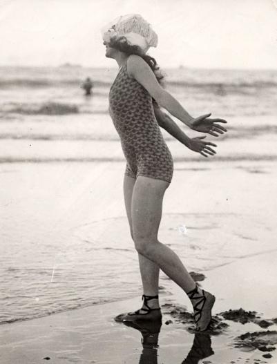 Strandleven : Vrouw met badpak en badschoenen aan kijkt met stralende lach en met zwierige armen naar de zee waar ze vlakbij staat. Engeland, 1922. Deze foto maakt deel uit van het zogenaamde badnummer van 1922 van het tijdschrift Het Leven.
