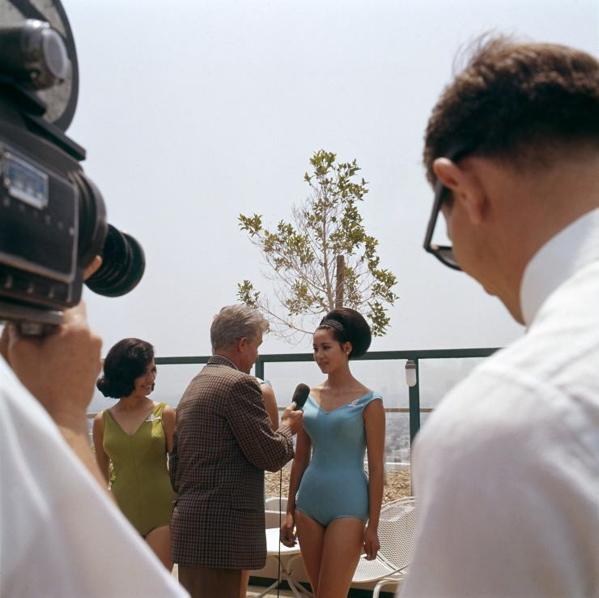 SFA002020440 Miss verkiezingen.  Onbekende deelneemster aan een Miss Universe verkiezing  wordt - in badpak -  ge﮴erviewd door een onbekende radio verslaggever. Links  vooraan: tijdens dit interview worden ook televisie [film] opnamen gemaakt.  Plaats en datum onbekend.