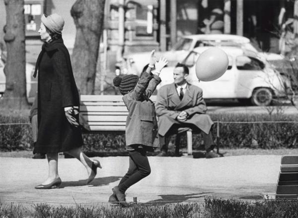 Kinderen met ballonnen, wedstrijden. Ieder jaar op de eerste dag van mei als de lange winter voorbij lijkt en de lente zijn intrede doet, dragen de studenten witte mutsen en spelen de kinderen met mei-ballonnen, Helsinki, Finland 1 mei 1964. Foto: Een klein meisje speelt met een ballon. SFA002012188