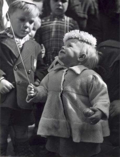 Klein meisje met wonderlijk hoofddeksel heeft een touwtje in haar rechter hand met daaraan, waarschijnlijk, een ballon. In haar andere hand een rond voorwerp aan een touwtje. Nederland, plaats onbekend, [ca. 1950-1955] SFA002018862