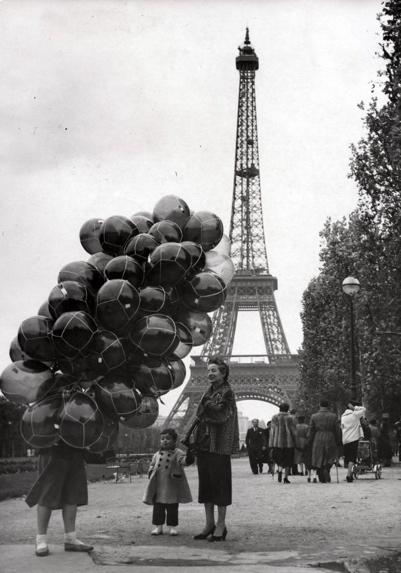 Ballonverkopers. Er zijn zoveel ballons waaruit de kleine jongen kan kiezen, Parijs, Frankrijk 2 november 1953. Op de achtergrond de Eiffeltoren. SFA007003001