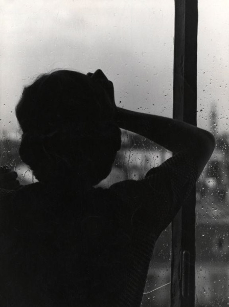 SFA003001294 | Silhouet van vrouw die uitkijkt naar beter weer door de ramen waar de regen tegenaanslaat. 1952. -[emotie, verlangen, somber]