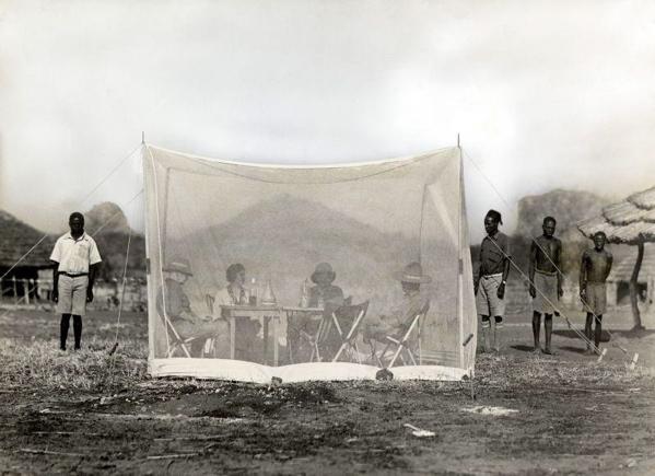 SFA003002463 | Afrika. Een transparante eetkamer (muskietennet).  De toeristen/ expeditieleden zitten in een grote klamboe beschermd tegen de muggen te eten terwijl de inboorlingen buiten de tent wachten.