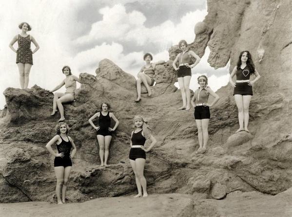 SFA022008474. Strand- en badmode. Negen jonge vrouwen poseren tegen een decor van 'rotsen'  de nieuwste badpakken. Zonder plaats, 1929.