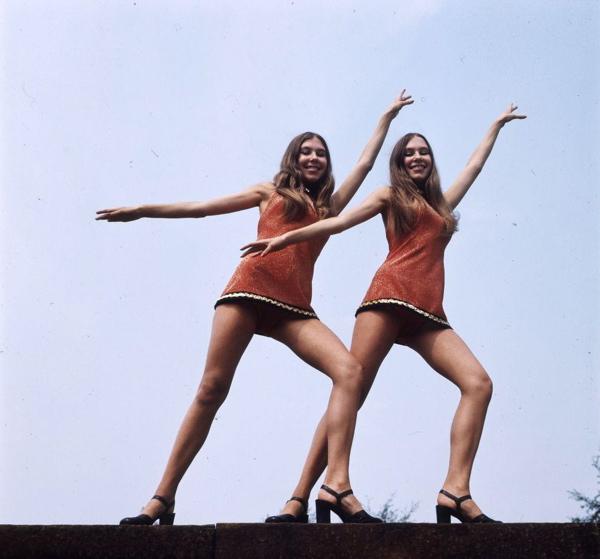 SFA001012249 Tweeling Daphne en Debbie (Deborah), voormalige showgirls in Parijs. De Nederlandse tweeling poseert in een kort lurex showjurkje in danshouding.