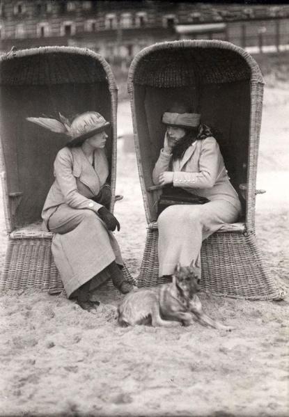 SFA003000127 Strandleven.Twee dames zitten op het strand te praten in rieten strandkorven (strandstoelen) Plaats en land onbekend, 1913.