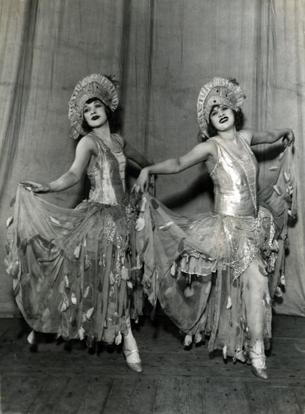 """SFA022827414 Dansen, duo's. De danseressen """"Les Swanson Sisters"""" in fantasierijke danskostuums van glanzende en transparante stof tijdens een uitvoering van een zang-dansnummer in de Champs Elysees; Music Hall"""". Parijs, Frankrijk, 1926."""