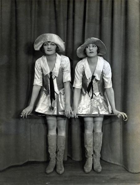 SFA022827416 Dansen, danseressen. Dansduo in glanzend satijn met hoed, stok en lange laarzen tijdens een dansuitvoering. Engeland, 1926.