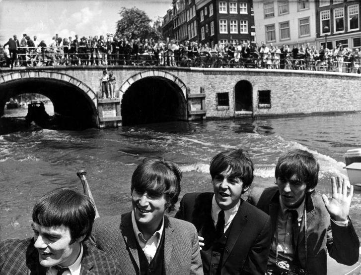 SFA001005282 Britse popgroep The Beatles in Amsterdam, rondvaart door de grachten. Vanaf bruggen juichen honderden fans ze toe. V.l.n.r. invallende drummer Jimmy Nichol, John Lennon, Paul McCartney en een terugzwaaiende George Harrison. Amsterdam, 6 juni 1964.