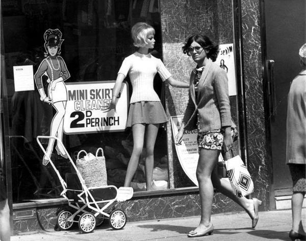 SFA001010633 Minimode, de rokken gaan omhoog, de prijzen omlaag. Stomerijen hebben besloten dat de prijs voor het stomen van een minirok 2 pence per inch is.  Vrouw in mini-jurk passeert een stomerij met een etalagepop in minirok en een bordje met 'Miniskirts cleaned 2d per inch'. Londen, 29 juni 1968.