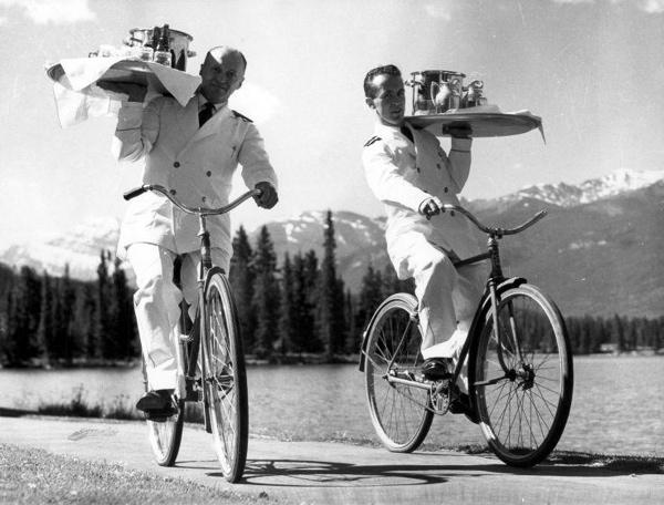 """SFA001014379 Fietsende kelners: In een vakantie-park (""""Jasper Park Lodge"""") in het Canadese Jasper National Park brengen twee kelners, met elk een dienblad vol eten en drinken, in witte pakken op de fiets de maaltijd rond, (vanuit het centrale gebouw naar de omliggende vakantiehuisjes), 20 juni 1960."""