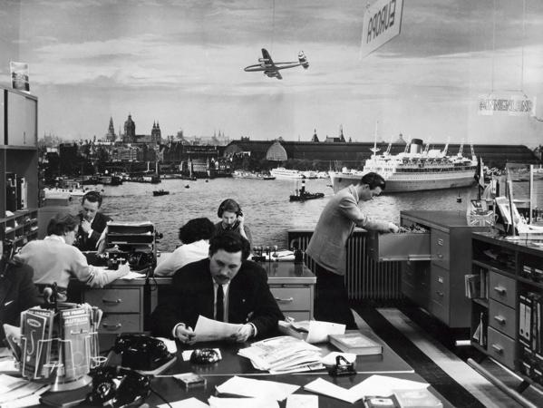 SFA002022906 Fotografie.Interieur van het reisbureau Hoyman en Schuurman waar iedereen aan het werk is, met aan de wand een levensechte foto van het IJ in Amsterdam, en alles wat daar omheen gebeurt, Nederland 9 april 1958.
