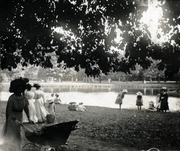 SFA022009607 Stadsparken. Vrouwen en kinderen met hoedjes bij een waterpartij in het Vondelpark. Links op de voorgrond vrouw met kinderwagen. Nederland, Amsterdam, 1911.