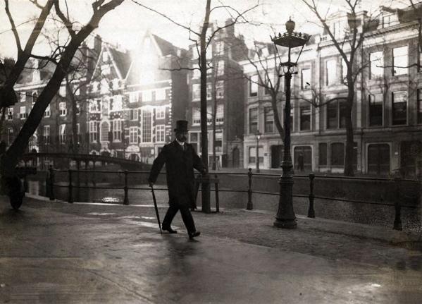 SFA022009711 Amsterdam/sfeerbeeld. Een kwieke heer met wandelstok wandelt in de morgenzon langs de Oudezijds Voorburgwal. Op de achtergrond de Bank van Lening. Foto 1910.