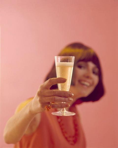 Toast, drinken: vrouw houdt lachend haar glas omhoog.