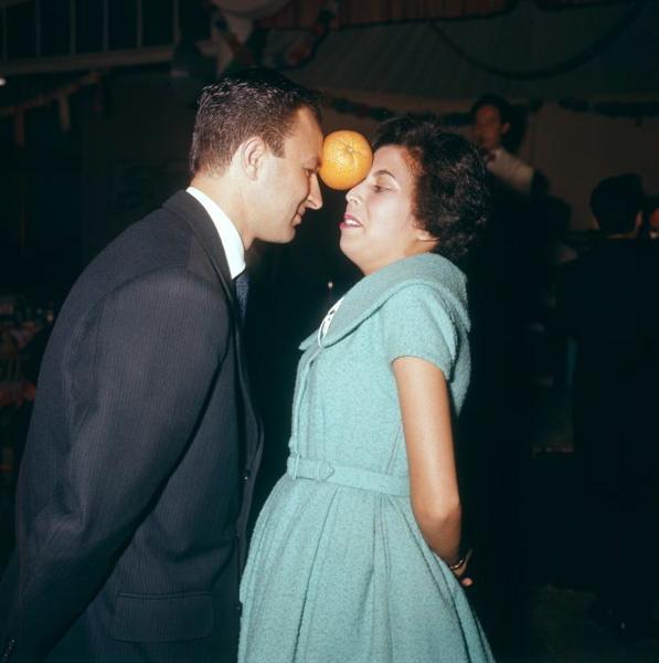 SFA002020433 Miss Sinaasappel . Krampachtig probeert het dansende paar een sinaasappel op de  plaats te houden. Wanneer de vrucht valt is het paartje uitgeschakeld. 1959. Plaats  onbekend.
