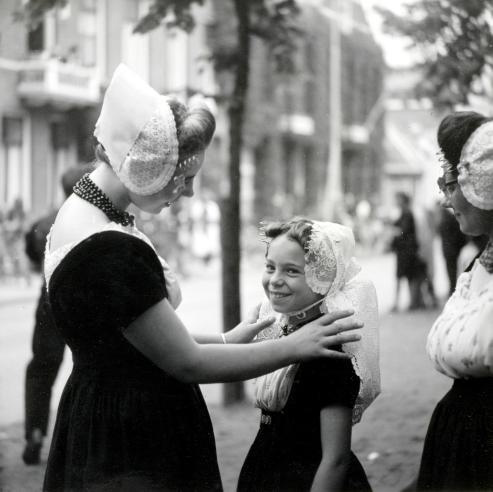 Twee vrouwen  met jong meisje in Zeeuwse klederdracht.