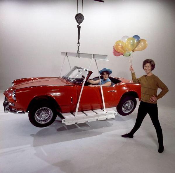 Automerken, auto's. Rode Triumph Spitfire  op een weegschaal of wordt opgetild door een kraan, naast een vrouw met een tros ballonnen. Nederland, ca. 1970. SFA001009987