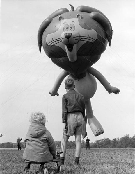 Twee kinderen kijken op naar een enorme heliumballon in de vorm van Linus the  lion. Ohio, Verenigde Staten van Amerika, 24 oktober 1964. SFA004001865