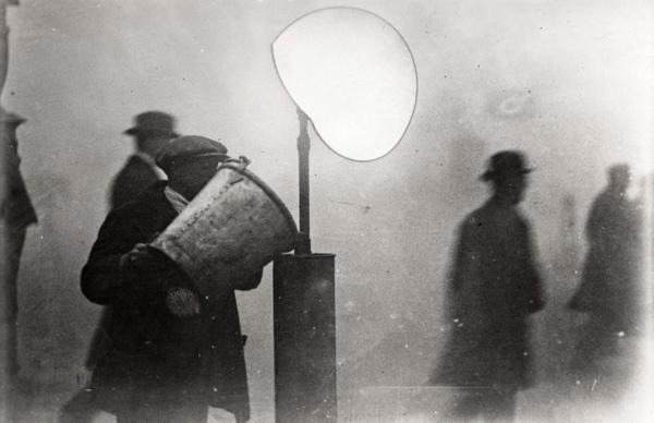 Ballonverkopers. Ballonverkoper giet water op carbid, om de ballon op te  blazen, [Engeland 1920-1940]. (Mistig beeld) SFA007002995