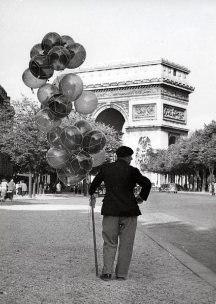 Ballonverkopers. Een ballonverkoper heeft ondanks dat hij zijn prijzen heeft verlaagd, nog steeds geen klanten in de vakantietijd, Parijs, Frankrijk 25 juni 1949. Op de achtergrond de Arc de Triomphe. SFA007003000