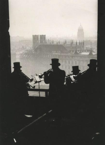 SFA007002363 | Silhouet van vier mannen met hoge hoeden die met blaasmuziek het Nieuwe Jaar inluiden vanaf de Domtoren in Berlijn. Op de achtergrond daken en kerktorens van de stad. Berlijn, [1931].