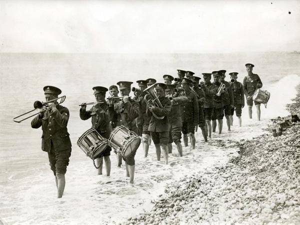 SFA022801853 | Eerste Wereldoorlog, Engelse leger. De militaire muziekkapel van het 12e bataljon Sherwood Foresters, tijdens een repetitie aan het strand van Belgie afkoeling zoekend in het water. Juli 1915.