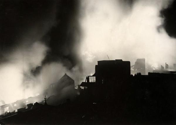 SFA022811337 | Brand. Silhouetten van de verbrande kaarsenfabriek steken af tegen de nachtelijke hemel. Er is een enorme rookontwikkeling onstaan. Gouda, Nederland, 1936.