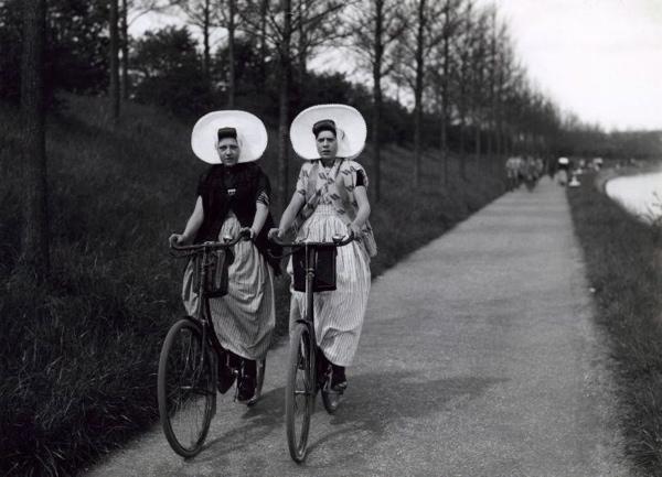 SFA003001222 Twee jongedames op de fiets in Zeeuwse klederdracht op een fietspad bij Arnemuiden, jaren '30.