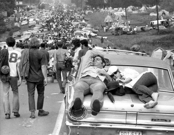 SFA001010975 Woodstock popfestival 1969. Stel slapend op de achterklep van ene auto in de lange stoet op weg naar het land van boer Max Yasgur bij Bethel in de staat New York. Verenigde Staten van Amerika.