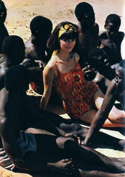 SFA002001551 Modefotografie. Modereportage in Afrikaans land. Blank fotomodel poseert in  badpak tussen lokale bevolking op het strand. Plaats en jaartal onbekend  [1965-1970].